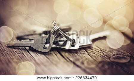 The Bunch Of Keys Lies On A Wooden Table.