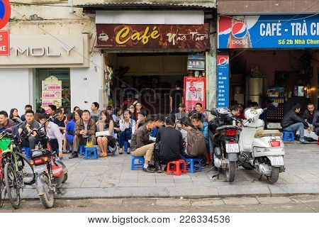 Hanoi, Vietnam - Mar 15, 2015: People Drink Coffee, Tea Or Juice Fruit On Cafe Stall On Sidewalk In