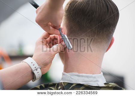 The Hairdresser Makes A Stylish Men's Hairstyle With A Dangerous Razor. Barber Shaves A Man's Shawl