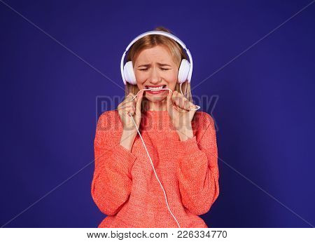 upset woman in headphones biting cord