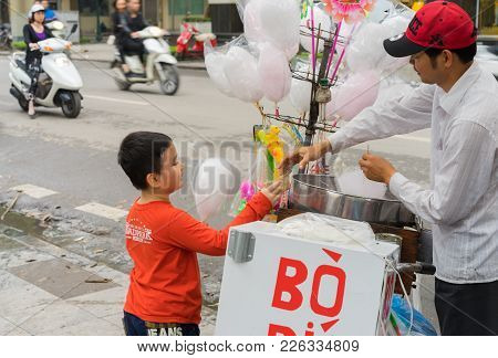 Hanoi, Vietnam - Mar 15, 2015: A Boy Buys Cotton Candy Floss From Vendor On Ly Thai To Street
