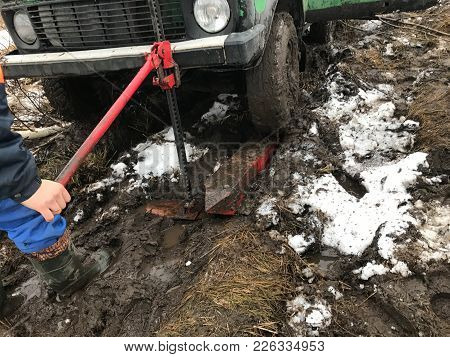 The Man Raises The Wheel Rack And Pinion Jack. Front Wheel Green Machine Raised Out Of The Mud By Me