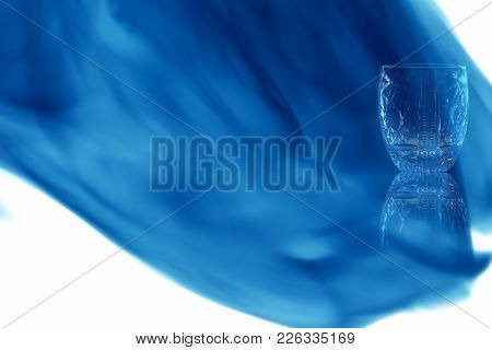 Empty Shot Of Vodka Or Tequila With Pattern On White Background Enveloped In Puff Of Blue Smoke. Pla
