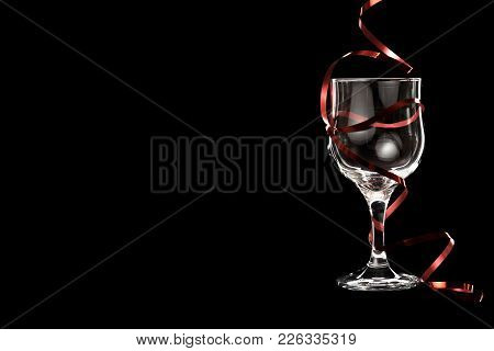 Empty White Wine Glass With Red Ribbon Isolated On Black Background. Place For Your Text.