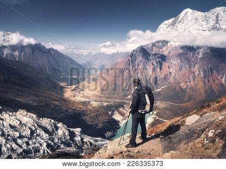 Standing Sporty Man With Backpack On The Mountain Peak And Beautiful Mountains Atbright Sunny Day. L