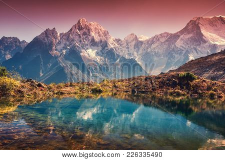 Mountains With Snow Covered Peaks, Red Sky Reflected In Lake