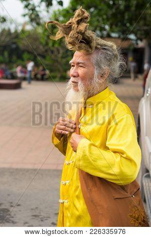 Quang Ninh, Vietnam - Mar 22, 2015: Portrait Of Old Vietnamese Man With Very Long Hair. He's Wearing