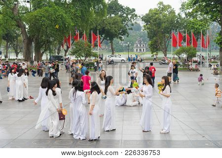 Hanoi, Vietnam - Apr 5, 2015: Group Of Students In Vietnamese Traditional Dress Ao Dai Taking Photo