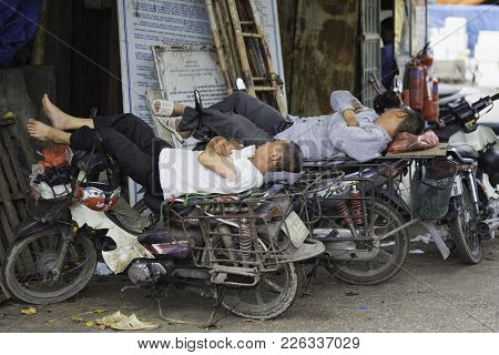 Hanoi, Vietnam - Aug 28, 2015: Motorcycle Drivers Sleep During Lunch Time At Long Bien Market
