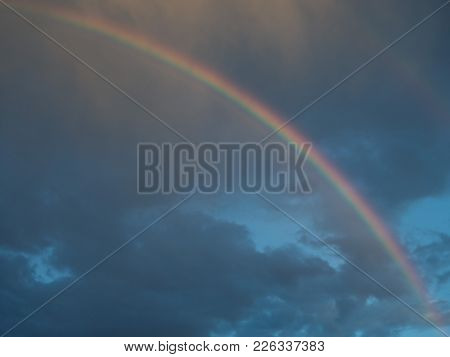 Large Bright Rainbow In The Blue Sky Amidst Gray Rain Clouds.