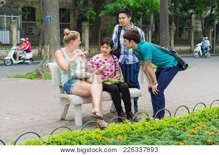 Hanoi, Vietnam - Apr 5, 2015: Group Of Students Learn To Speak English With English Native Foreigner