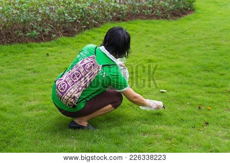 Hanoi, Vietnam - Apr 19, 2015: A Woman Picking Up Litter In The Park At Times City, A Luxury And Hig