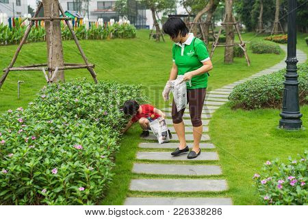 Hanoi, Vietnam - Apr 19, 2015: Family Volunteers Picking Up Litter In The Park At Times City, A Luxu