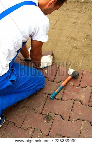 The Master Paves The Paving Slab Professionally