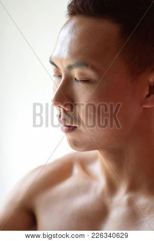 A Side Profile Of An Asian Chinese Male With His Eyes Closed
