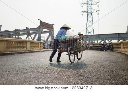 Hanoi, Vietnam - Oct 25, 2015: Woman Vendor Trying To Push Her Fruit Loaded Bike On Sloppy Street On