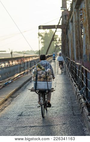 Hanoi, Vietnam - July 23, 2016: Back View Of Street Woman Vendor Carrying Fruit On Bike On Long Bien