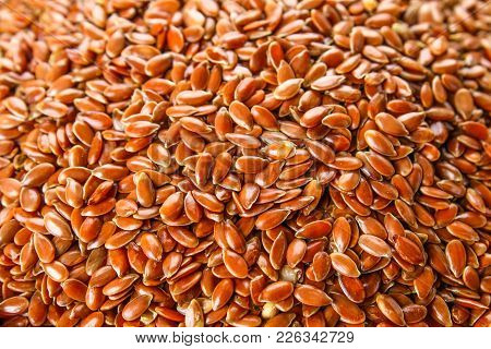 Many Flax Seeds Are Scattered In The Background, And Poured Into A Clay Plate