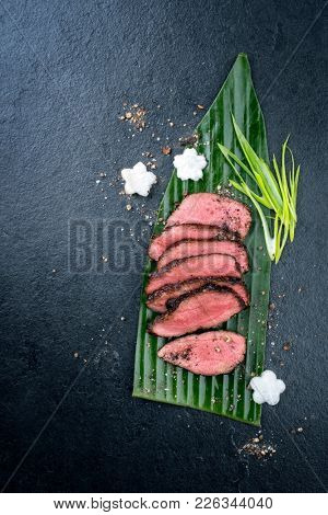 Japanese barbecue wagyu aged fillet steak slices with daikon and leek as top view on a banana leaf