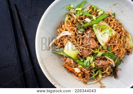 Traditional stir-fried Thai phat mama mie noodles with pork and vegetables as top view in a bowl with copy space left