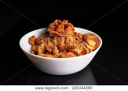 Greaves Crunchy Cracklings Fried Pork Lard Crust On Black Reflective Studio Background. Isolated Bla