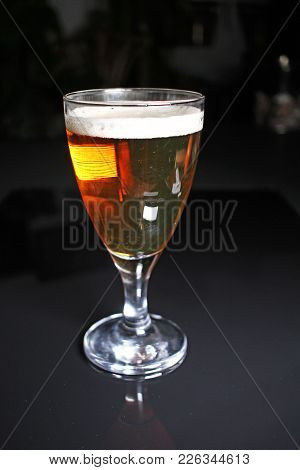 Beer On Glass On Black Reflective Studio Background. Isolated Black Shiny Mirror Mirrored Background