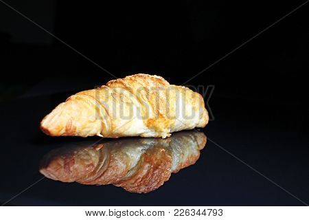Croissant On Black Reflective Studio Background. Isolated Black Shiny Mirror Mirrored Background For
