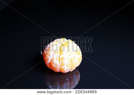 Peeled Mandarin On Black Reflective Studio Background. Isolated Black Shiny Mirror Mirrored Backgrou