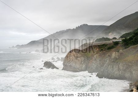 Beautiful Landscape Of The Rocky Shoreline On The Foggy Background Of The Stormy Ocean And The Sky O