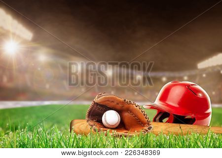 Baseball Helmet, Bat, Glove And Ball On Grass In Brightly Lit Outdoor Stadium With Focus On Foregrou