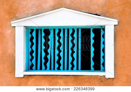 Adobe Wall Has White Framed Window With Turquoise Blue Decorative Woodwork.