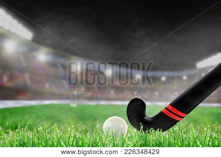 Field Hockey Stick And Ball On Grass In Brightly Lit Outdoor Stadium With Focus On Foreground And Sh