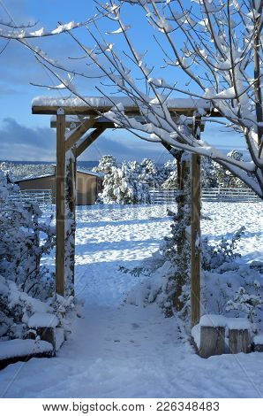 Wooden Garden Entrance Opens Out Into A Winter Wonderland.  Snow Fills New Mexico Farm.