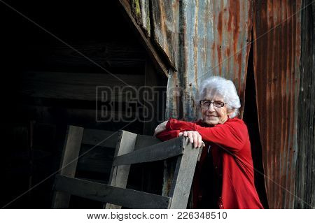 Elderly Woman Leans Against Part Of The Old Family Barn In Arkansas.  She Is White Haired And Wears