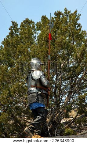 Soldier Carrying A Halberd Marches Upward.  He Is Wearing A Helmet And Armor.