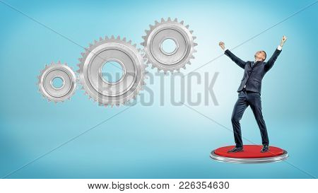A Victorious Businessman Stands On A Giant Red Push Button Near Three Interlocking Gears. Successful