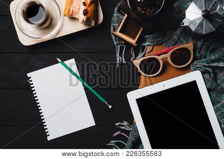 Wooden Black Table With Tablet,glasses,notebook And Cup Of Coffee.top View.