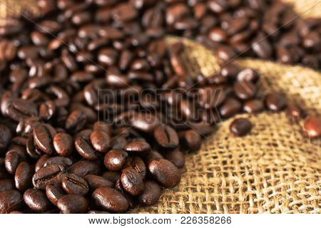 An abstract image of roasted coffee bean on top of a burlap sack.