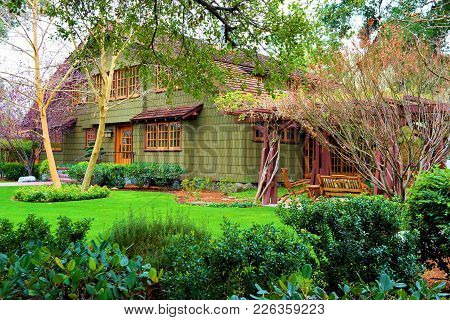 Contemporary Style Home With A Rustic Design Surrounded By A Lush Green Garden With Manicured Landsc