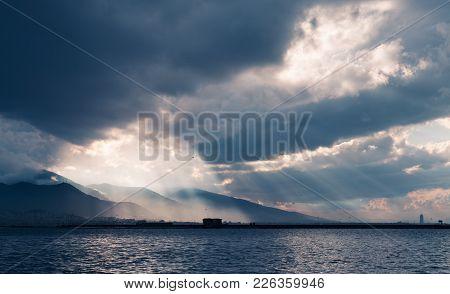 Dark Stormy Clouds With Sunbeams, Landscape Background Photo, Bay Of Izmir City, Turkey