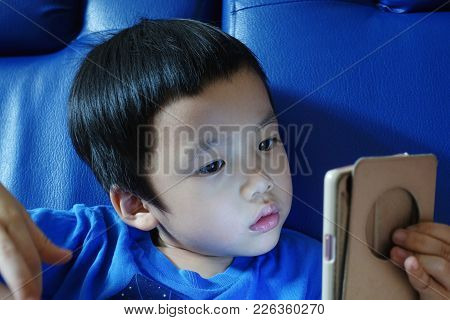 Young Asian Kid Staring At Phone With Blue Background