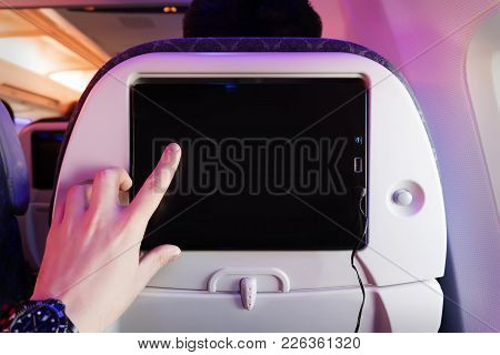 Aircraft Monitor The Passenger Seat. Interior Plane. Touch Screen. Male Finger Taps On The Screen. B