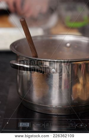 Saucepan And Wooden Spoon. Restaurant Kitchen With Equipment For Cooking.