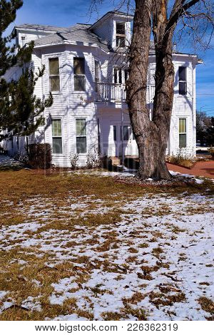 Large Well Kept Up Older Home With A Large Front Yard Covered In Snow Taken In A Rural Community