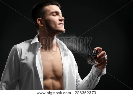 Handsome man in unbuttoned shirt and with bottle of perfume on dark background