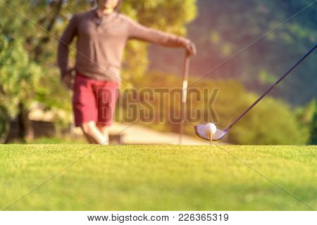 Golf Ball Tee Off On The Green.  Couple Golf Player Putting Golf Ball In The Background.  Lifestyle