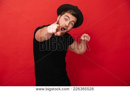 Picture of handsome cheerful man wearing black t-shirt and hat having fun and pointing fingers on camera meaning hey you isolated over red wall