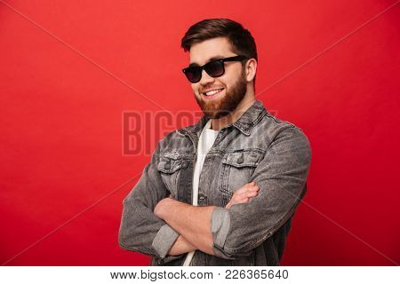 Portrait of irresistible stylish man 30s in sunglasses smiling on camera and posing with hands crossed isolated over red background