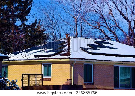Middle Class Home With Modern Solar Panels On The Roof After A Snow Storm