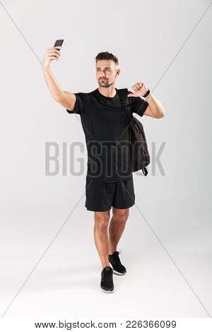 Full length portrait of a smiling mature sportsman with backpack taking a selfie and pointing finger at himself isolated over gray background